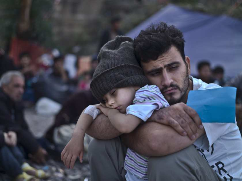a-syrian-refugee-child-sleeps-on-his-fathers-arms-while-wait