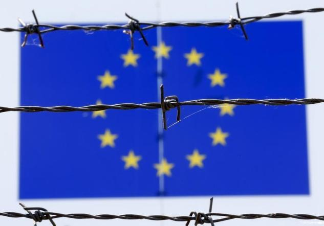 FILE PHOTO: A barbed wire is seen in front of a European Union flag at an immigration reception centre in Bicske