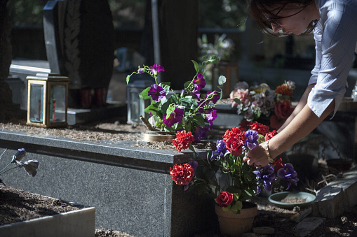 Woman putting flowers on tomb